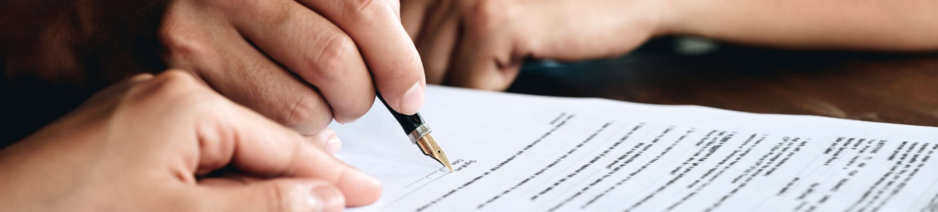 a person signing documents at Augusta civil litigation attorney office